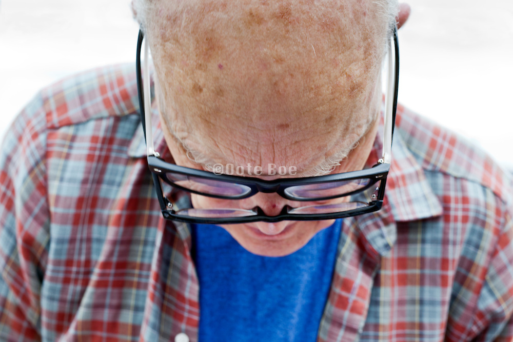 senior man using two glasses to read