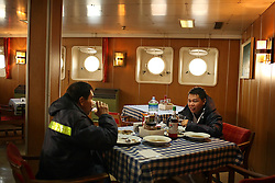 Filipino workers take a lunch break aboard the Alfa K, a Mediterranean based bulk carrier with a Panamanian flag, which was undergoing repairs at the port of Piraeus in Greece on Feb. 20, 2008. Inspectors impose ITF-standard treaties on ship-owners to guarantee minimal standard working conditions for seafarers. They are on call 24 hours a day to address concerns from workers coming to port on the international ships.