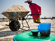 "28 MARCH 2014 - NA KHOK, SAMUT SAKHON, THAILAND:  A worker in a salt field pushes a wheel barrow of salt past a cooler of iced tea. Thai salt farmers south of Bangkok are experiencing a better than usual year this year because of the drought gripping Thailand. Some salt farmers say they could get an extra month of salt collection out of their fields because it has rained so little through the current dry season. Salt is normally collected from late February through May. Fields are flooded with sea water and salt is collected as the water evaporates. Last year, the salt season was shortened by more than a month because of unseasonable rains. The Thai government has warned farmers and consumers that 2014 may be a record dry year because an expected ""El Nino"" weather pattern will block rain in mainland Southeast Asia. Salt has traditionally been harvested in tidal basins along the coast southwest of Bangkok but industrial development in the area has reduced the amount of land available for commercial salt production and now salt is mainly harvested in a small parts of Samut Songkhram and Samut Sakhon provinces.    PHOTO BY JACK KURTZ"