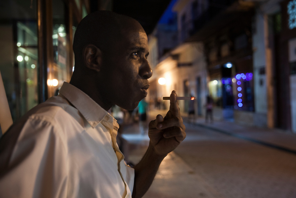 Young man smoking at night at a street in Old Havana, Cuba.