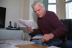 Retired James Gosling, 58,  sorts through the paperwork that has accumulated in his long running dispute with Camden council that began when his flat was flooded with sewage. West Hampstead, London, October 25 2018.