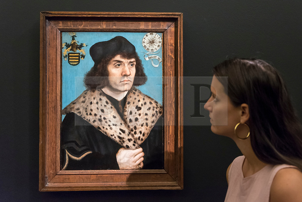 """© Licensed to London News Pictures. 29/06/2018. LONDON, UK. A staff member views """"Portrait of a man with a spotted fur collar"""" by Lucas Cranach The Elder (Est. £1.5-2m).  Preview of Old Masters, British, Treasures, Sculptures and Ancient works at Sotheby's New Bond Street to be offered for sale on 3 and 4 July 2018.  Photo credit: Stephen Chung/LNP"""