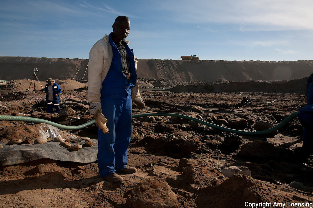 ORANJEMUND, NAMIBIA -- SEPTEMBER 25: Namdeb mine workers dig with shovels and use a trans vac (giant vacuum) to clear the site of a shipwreck on September 25, 2008 in Oranjemund, Namibia. The wreck was discovered by miners in the Namdeb diamond mine off the coast of Namibia. The ship was found seven meters below sea level on April 1, 2008. Archeologists presume the wreck is from the early 1500s. Most of the the artifacts found are being stored in a storage shed at the Namdeb Diamond Mine. Items include: copper ingots, bronze canons, canon balls, pewter bowls and plates, ivory tusks from African elephants, and most substantial over 2000 gold coins- approximately 21 kg - the most gold found in Africa since the Valley of the Kings in Egypt. (Photo by Amy Toensing) _________________________________<br /> <br /> For stock or print inquires, please email us at studio@moyer-toensing.com.