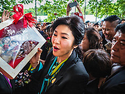 05 AUGUST 2016 - BANGKOK, THAILAND: YINGLUCK SHINAWATRA accepts a gift of small dolls in her likeness while she walks through a mob of supporters at the Supreme Court of Thailand Friday. She appeared in court to start her legal defense. She was deposed by a military coup in 2014 and is being tried on corruption and mismanagement charges related to a price support plan for Thai rice farmers that was instituted while she was Prime Minister. More than two years after her government was deposed by a military coup, she is still a popular figure and hundreds of her supporters packed the area around the courthouse to greet her when she arrived at the Court.       PHOTO BY JACK KURTZ