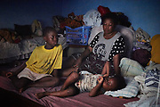 Kadiatu Juo, 36 years old with her two daughters, from left, Francesca Juo, 9 years old and Alfreda Juo, 3 years old in Kenema District, Sierra Leone on June 6, 2017. Kadiatu's 12 year old son George recently died of malaria.<br /> <br /> &ldquo;On a Saturday, a few days after he had taken his National Primary School Examination (NPSE), he had fever. He was vomiting a lot so we took him to hospital the next day because he had become very weak. They tried to treat him there but unfortunately he didn&rsquo;t survive. He was exposed to mosquito bites because he wasn&rsquo;t sleeping under a bed net,&quot; said Kadiatu.