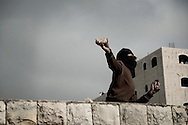 "JERUSALEM :  A masked Palestinian throws a stone to Israeli border policemen during clashes in the Shuafat refugee camp on March 16, 2010. Hundreds of Palestinians clashed with security forces in east Jerusalem as tension boiled over in the city and a senior Hamas leader called for a new ""intifada,"" or uprising."