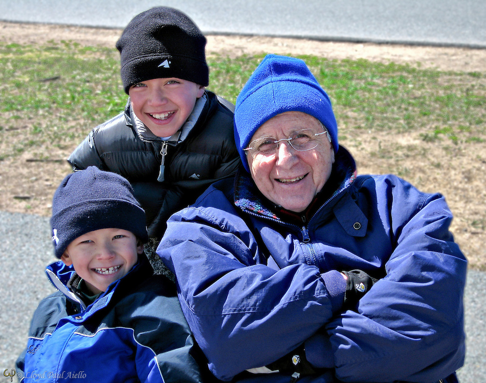 Ashlyn and Bryce smile with their Grandfather while seated on a stone chair at Back Beach in Rockport, MA