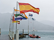 Flags wave in a brisk rainstorm at Punga Cove, Queen Charlotte Track, South Island, New Zealand