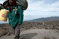 A porter on Mount Kilimanjaro carries a ruck sack and a jerry can full of water in front of a colorful group of clients.