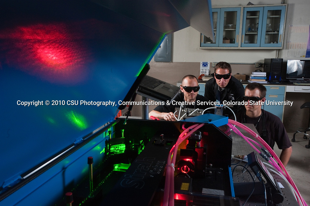Colorado State University Mechanical Engineering professor Anthony Marchese, center, works with PhD students Torben Grumstrup and Tim Vaughn on a laser setup to measure nitric oxide emissions emitted from burning biofuels.