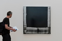 "© Licensed to London News Pictures. 07/06/2016. London, UK.   A visitor views ""Big Black Mirror"", by the American artist Mary Heilmann, which is previewed ahead of her first major UK exhibition, ""Looking at Pictures"", at the Whitechapel Gallery.  The exhibition spans the artist's five decade career, from her early geometric paintings made in the 1970s to her recent shaped canvases in day-glo colours.  The show features approximately 45 paintings as well as a selection of ceramics, chairs and works on paper, many of which have never been exhibited.  Photo credit : Stephen Chung/LNP"