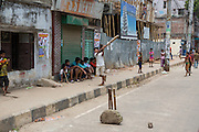 Children playing a game of street cricket in Dhaka, Bangladesh.