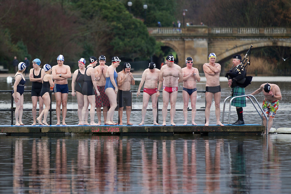© Licensed to London News Pictures. 25/12/2012. London, UK. Members of the Serpentine Swimming Club line a jetty as they prepare to compete in the Serpentine Swimming Club's annual Christmas morning 'Peter Pan Cup' race in Hyde Park, London, today (25/12/12).   The race, which takes place every Christmas Day on the Serpentine River, takes its name from from the novel by J.M.Barrie after the author presented the first Peter Pan Cup in 1904. Photo credit: Matt Cetti-Roberts/LNP