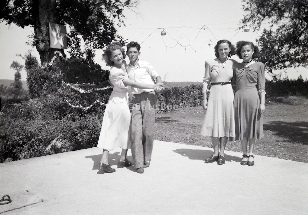 young couple and two girls on the dancing floor in a rural environment