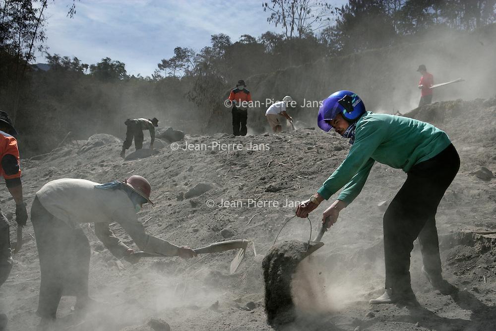 Indonesie.Jogjakarta.Juni 2006.<br /> Hulpverleners en locale mensen uit het natuurrampgebied rond Jogjakarta helpen mee de weg vrij te maken van lagen vulkaanas as gevolg van de recente vulkaanuitbarsting.<br /> Foto:Jean-Pierre Jans/de Volkskrant