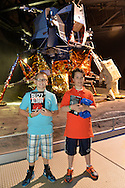 "May 11, 2013 - Garden City, New York U.S. -  Two smiling boys pose holding their copies of Buzz Aldrin's new book ""Mission to Mars"" that the astronaut signed for them at the Cradle of Aviation Museum book signing, in front of LEM 13, the Grumman Lunar Module scheduled for Apollo 19, which was canceled."