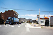 Een vrachtwagen passeert het eens fameuze Goldfield Hotel uit 1905 (links) en de Dahlstrom garage uit 1930. Goldfield, Nevada, is een bijna verlaten ghost town in Esmeralda County, gelegen aan de State Route 95. Tussen 1906 en 1910 was Goldfield de grootste plaats in de Amerikaanse staat Nevada met meer dan 20.000 inwoners. Momenteel leven er tussen de 200 en 300 mensen. Het plaatsje is groot geworden door de vondst van goud in 1902. Vanaf 1910 daalde het aantal inwoners snel en in 1923 is een groot deel verwoest door een brand. De overgebleven huizen zijn grotendeels verlaten, maar worden nog altijd onderhouden door de inwoners. Daarmee wordt de geschiedenis van de het plaatsje bewaard.<br /> <br /> A big tuck passes the once famous Goldfield Hotel of 1905 (left) and the Dahlstrom&rsquo;s Garage of 1930. Goldfield, Nevada, is an almost deserted ghost town in Esmeralda County. Between 1906 and 1910, Goldfield was the largest town in the state of Nevada with more than 20,000 inhabitants. Currently, there are between 200 and 300 people. The town has grown with the discovery of gold in 1902. From 1910, the population declined rapidly, and in 1923 the town was largely destroyed by a fire. The remaining houses are largely abandoned, but are still maintained by the residents. This way the history of the town is preserved.