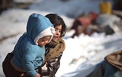 An Afghan refuge girl holds her brother as she walks at a refugee camp, Kabul, Afghanistan, January 2, 2013. Photo by Imago / i-Images...UK ONLY