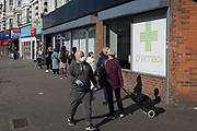 As the number of UK Coronavirus cases rose to over 8,000, it was announced that thousands of 15-minute home tests could be made available within days to those self-isolating with symptoms. South Londoners aware of social distance queue outside a branch of the pharmacy and health product retailer, Superdrug on the Walworth Road, on 25th March 2020, in London, England.