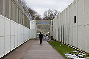 A visitor walks through the secure grounds of the prison. HMP Send, closed female prison. Ripley, Surrey.