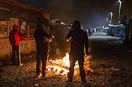 Calais, Pas-de-Calais, France - 24.10.2016    <br />  <br /> Refugees warm on a fire. Start of the eviction on the so called &rdquo;Jungle&quot; refugee camp on the outskirts of the French city of Calais. Refugees and migrants leaving the camp to get with buses to asylum facilities in the entire country. Many thousands of migrants and refugees are waiting in some cases for years in the port city in the hope of being able to cross the English Channel to Britain. French authorities announced a week ago that they will evict the camp where currently up to up to 10,000 people live.<br /> <br /> <br /> Fluechtlinge waermen sich an einem Feuer. Beginn der Raeumung des so genannte &rdquo;Jungle&rdquo;-Fluechtlingscamp in der franz&ouml;sischen Hafenstadt Calais. Fluechtlinge und Migranten verlassen das Camp um mit Bussen zu unterschiedlichen Asyleinrichtungen gebracht zu werden. Viele tausend Migranten und Fluechtlinge harren teilweise seit Jahren in der Hafenstadt aus in der Hoffnung den Aermelkanal nach Gro&szlig;britannien ueberqueren zu koennen. Die franzoesischen Behoerden kuendigten vor einigen Wochen an, dass sie das Camp, indem derzeit bis zu bis zu 10.000 Menschen leben raeumen werden. <br /> <br /> Photo: Bjoern Kietzmann
