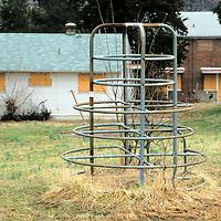 Playground equipments stands amid abandoned housing in Alexandria, VA.