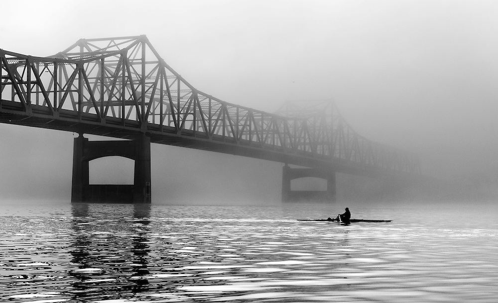 A rower on the Illinois River passes the Murray Baker Bridge in Peoria, Illinois as a fog recedes from the river valley. ©David Zalaznik