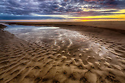 Sunrise reflection in a tide pool on a Corolla beach at Outer Banks, NC.
