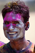 Indian man celebrating annual Hindu Holi festival of colours with powder paints in Mumbai, formerly Bombay, Maharashtra, India