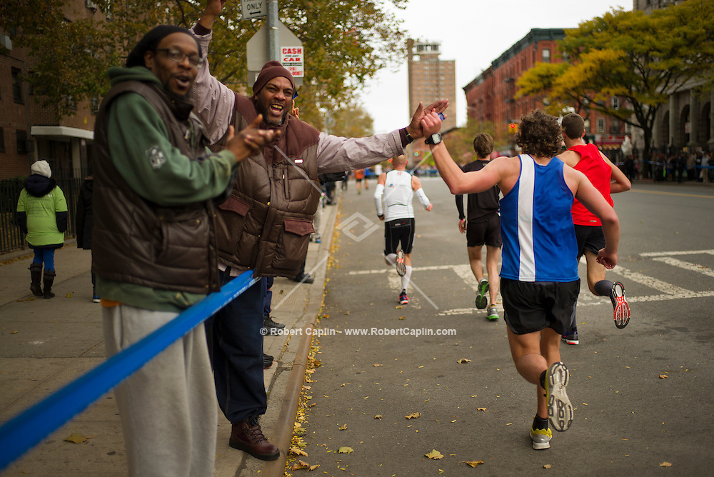 New York, New York - November 1, 2013 - Paul Kimble gives Marathon runners high-fives and cheers them on in The Bronx. <br /> <br /> Credit: Photo by Robert Caplin