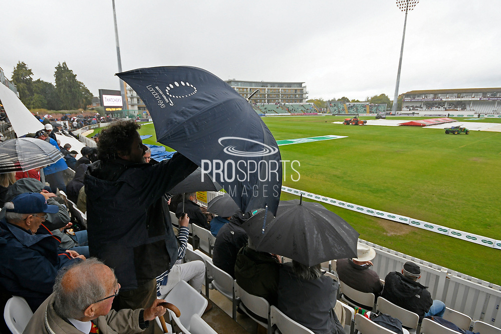 Umbrellas are up in the stands and covers are on as a shower passes over during the delay in play during the Specsavers County Champ Div 1 match between Somerset County Cricket Club and Essex County Cricket Club at the Cooper Associates County Ground, Taunton, United Kingdom on 25 September 2019.