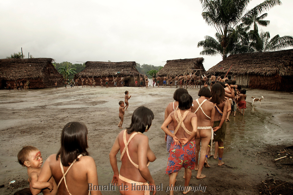 Viriunaveteri, Venezuela. Yanomami women dancing a tribal dance..The village of Viriunaveteri consists of 15 huts around a muddy square. It's situated in the Venezuelan Amazone several days by boat from the nearest town. This community on the banks of the Casiquiare is one of the few Yanomami villages that actually has some contact with the outside world. Most other tribes live deeper in the jungle.
