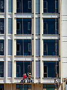 """15 FEBRUARY 2019 - SIHANOUKVILLE, CAMBODIA: Cambodian workers paint the exterior of a new Chinese apartment building in Sihanoukville. There are about 80 Chinese casinos and resort hotels open in Sihanoukville and dozens more under construction. The casinos are changing the city, once a sleepy port on Southeast Asia's """"backpacker trail"""" into a booming city. The change is coming with a cost though. Many Cambodian residents of Sihanoukville  have lost their homes to make way for the casinos and the jobs are going to Chinese workers, brought in to build casinos and work in the casinos.      PHOTO BY JACK KURTZ"""