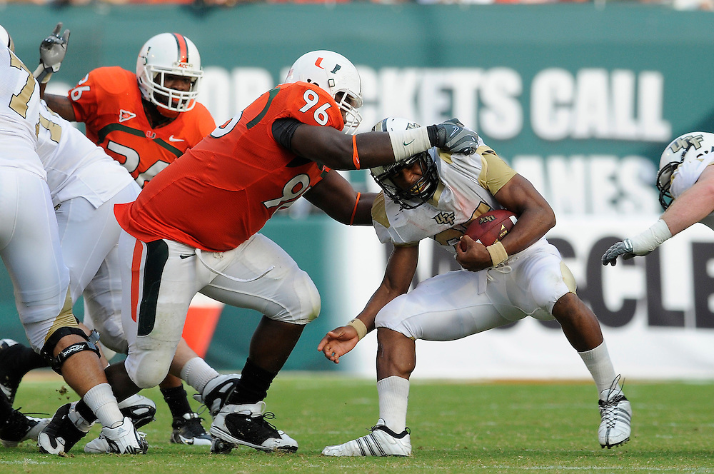 October 11, 2008 - Miami Gardens, FL<br /> <br /> University of Central Florida running back Ronnie Weaver is tackled by University of Miami defensive lineman Antonio Dixon during the Hurricanes 20-14 victory over the Knights at Dolphin Stadium in Miami Gardens, Florida.<br /> <br /> JC Ridley/CSM