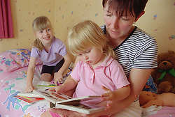 Mother reading with daughter in bedroom; older sister kneeling on bed with colouring book,