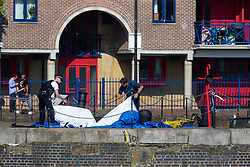 Following three reported deaths from drowning on the River thames on Tuesday 23 July as a heatwave grips the UK, police erect a tent as a body is recovered by police divers at Shadwell Basin in Wapping, a former riverside cargo dock, now converted to residential use. London, July 24 2019.