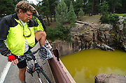 """""""Jimbo"""" Buickerood, Public Lands Coordinator for San Juan Citizens Alliance, takes a moment from his bike ride to check up on the progression of toxic wastewater contaminating the Animas River, as it makes its way south towards Durango, Colorado."""