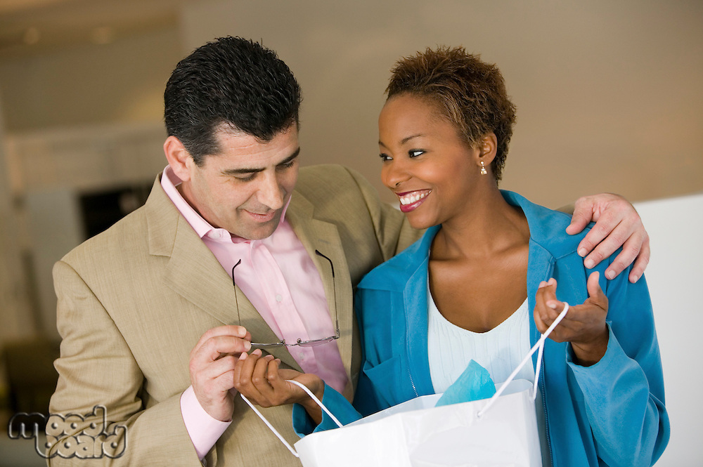 Woman Showing Man Purchases in Shopping Bag