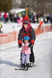 An instructor and her young student use the tow rope at the Quechee Ski Hill in Quechee, Vermont. Model Release.