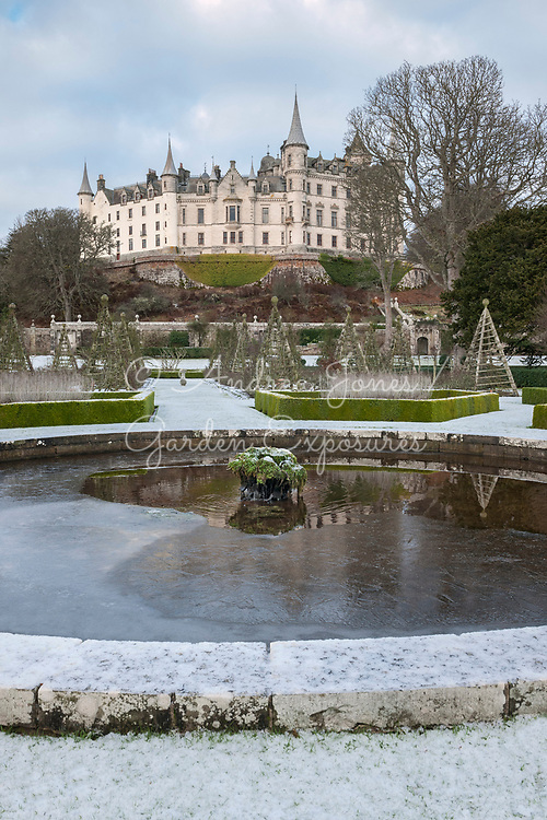 Snow covering the West Parterre, circular pond, Pyramid climbing plant supports and Dunrobin Castle<br /> <br /> <br /> Dunrobin Castle Sutherland, Scotland