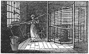 Spitalfields silk worker winding silk onto the warping frame: London. From 'Saturday Magazine' London, 16 November 1833. Woodcut.