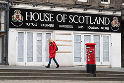 Edinburgh, Scotland, UK. 24 March, 2020.  Deserted streets in the heart of the Old Town tourist district in Edinburgh. All shops and restaurants are closed with very few people venturing outside following the Government imposed lockdown today. Pictured; woman passes a closed and covered up tourist gift shop on the Royal Mile. Iain Masterton/Alamy Live News