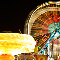Picture of carnival rides at night including a motion blurred spinning Ferris Wheel and chair swing ride. These rides are commonly found at carnivals, county fairs and amusement parks. Image is high resolution and is available as a stock photo, poster or print.
