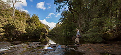A bushwalker rests beside a river on the Lees Paddock Track, near Mersey Forest, on the edge of  the Cradle Mountain Lake St Clair National Park in Tasmania.