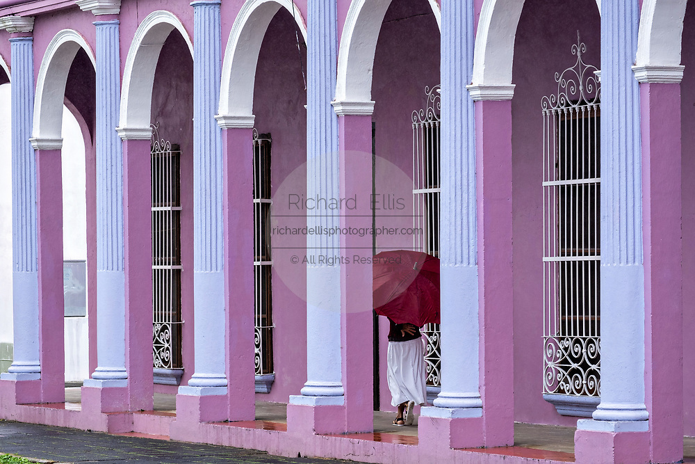 A woman with a red umbrella walks past a colorful colonnade style building in Tlacotalpan, Veracruz, Mexico. The tiny town is painted a riot of colors and features well preserved colonial Caribbean architectural style dating from the mid-16th-century.