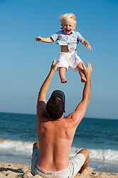 man throwing and catching a little boy in the air at the beach