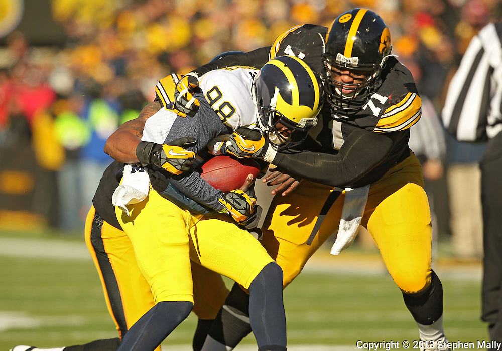 November 23 2013: Michigan Wolverines quarterback Devin Gardner (98) is sacked by Iowa Hawkeyes linebacker Christian Kirksey (20) and Iowa Hawkeyes defensive lineman Carl Davis (71) during the third quarter of the NCAA football game between the Michigan Wolverines and the Iowa Hawkeyes at Kinnick Stadium in Iowa City, Iowa on November 23, 2013. Iowa defeated Michigan 27-24. Iowa defeated Michigan 24-21.