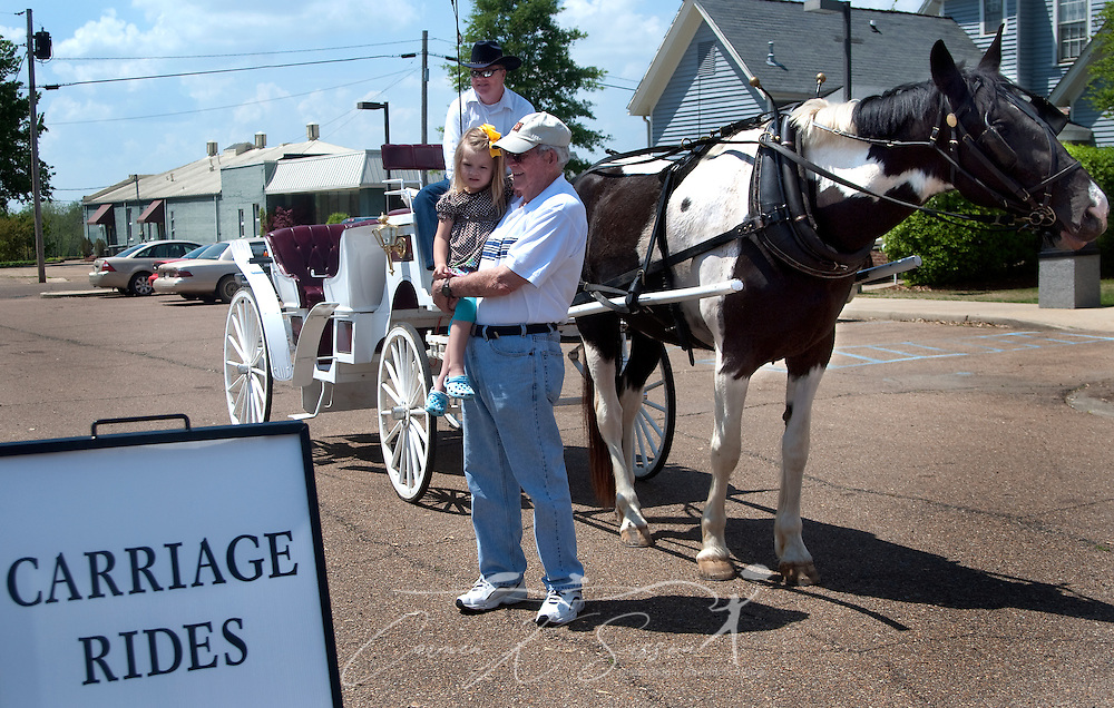 Bill Bailey holds his granddaughter, Gracie Black, as they wait for a horse-drawn carriage ride from driver Carl Woods at the Tennessee Williams Welcome Center in Columbus, Miss. April 17, 2010. Rides include stops at many of the historic, antebellum homes throughout the city. (Photo by Carmen K. Sisson/Cloudybright)