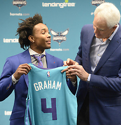 June 22, 2018 - Charlotte, NC, USA - Charlotte Hornets draft pick Devonte' Graham holds up his jersey with President of Basketball Operations & General Manager Mitch Kupchak during an introductory news conference at Spectrum Center in Charlotte, N.C., on Friday, June 22, 2018. (Credit Image: © David T. Foster Iii/TNS via ZUMA Wire)