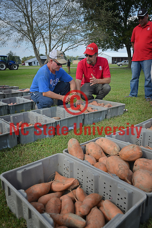 Extension agent (right) chats with a local farmer during Sweet Potato Days in Lenoir County.